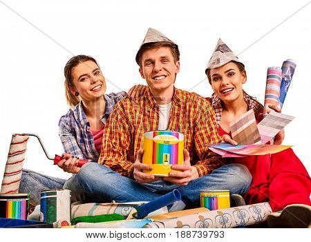 Repair group of people building home using paint roller tools and bank. Women and man in newspaper hat holding color guide renovation apartment.