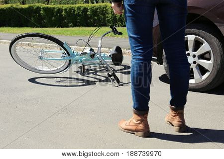 Young woman checking consequences of car and bicycle accident on street