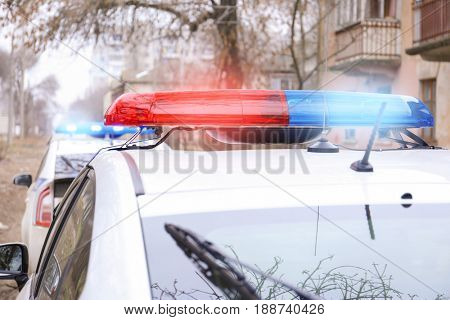 Police car with flasher on street, closeup