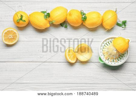 Squeezer and lemons on wooden table