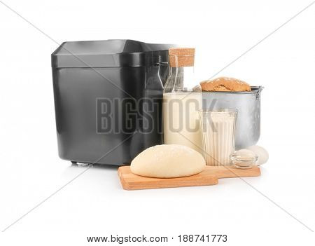 Bread machine, fresh loaf and ingredients for cooking on white background