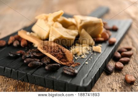 Cocoa butter, powder and beans on wooden board
