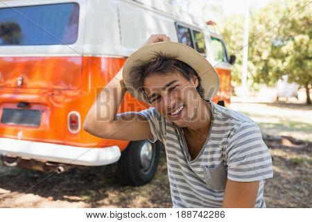 Portrait of man sitting in the park with camper van in background