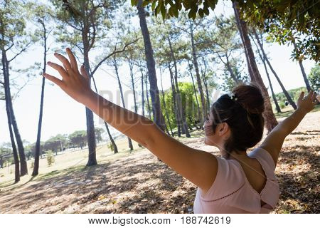 Blissful woman standing with arms outstretched in the park