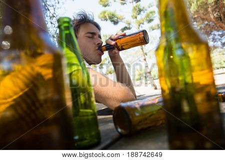 Unconscious man drinking beer from bottle in the park