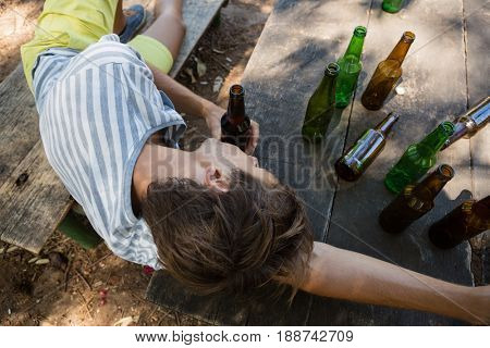 Unconscious drunk man lying on a bench in the park