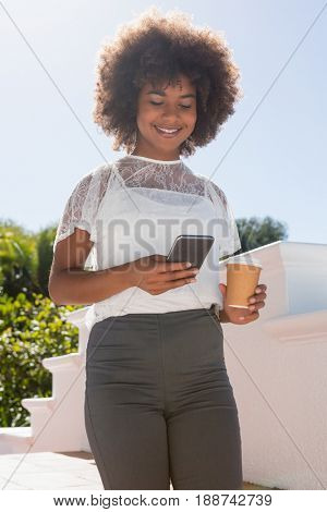 Smiling woman using mobile phone while holding disposable cup against sky on sunny day