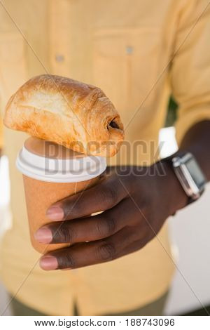 Mid section of man holding disposable coffee cup and baked bread