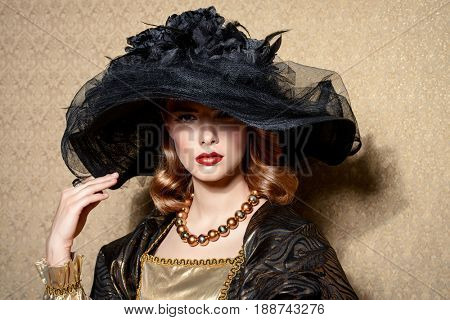 Portrait of a gorgeous young woman in elegant broad-brimmed hat and luxurious dress over golden background. Vintage style. Beauty, fashion.