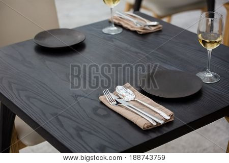 High angle view of eating utensils by wineglasses on table at restaurant