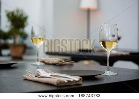 Wineglasses by eating utensils on table at restaurant