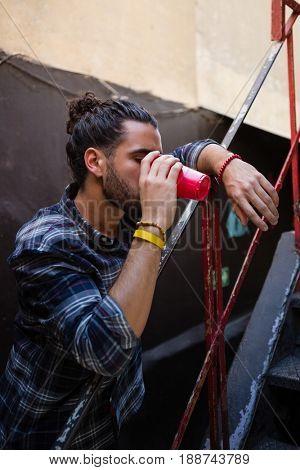 Man drinking alcohol at staircase of bar