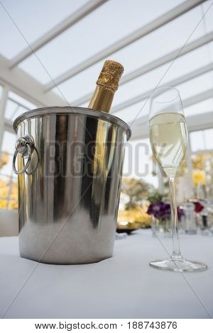 Low angle view of champagne bottle in bucket with glass on table in restaurant