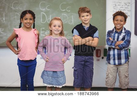 Portrait of smiling schoolkid standing in classroom at school