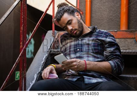 Man using mobile phone while having drink on staircase of bar