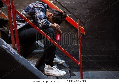 Drunk man sitting on staircase of bar