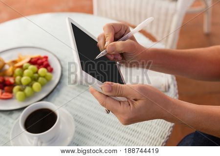 Cropped hands of woman using stylus on digital tablet at cafe