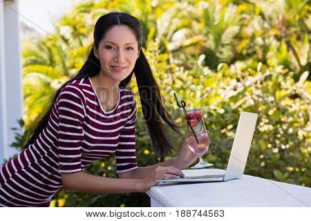 Portrait of young woman holding cocktail drink while using laptop on retaining wall