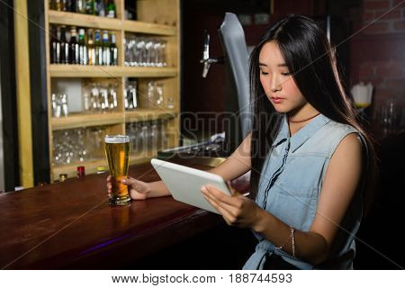 Woman using digital tablet while having beer at bar counter