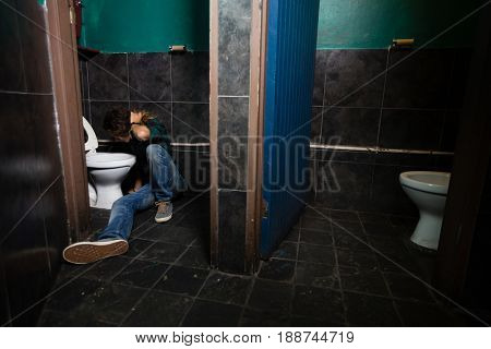 Man vomiting on toilet bowl in the washroom