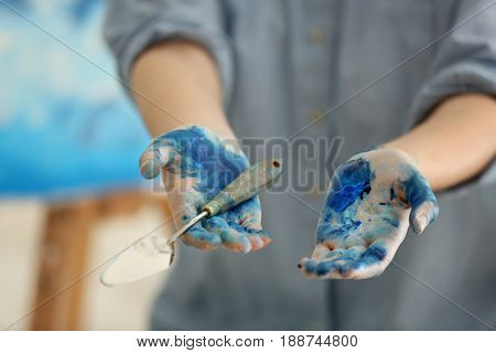 Female artist holding palette knife, closeup