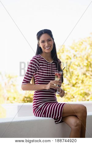 Portrait of smiling young woman holding cocktail while sitting on retaining wall at restaurant
