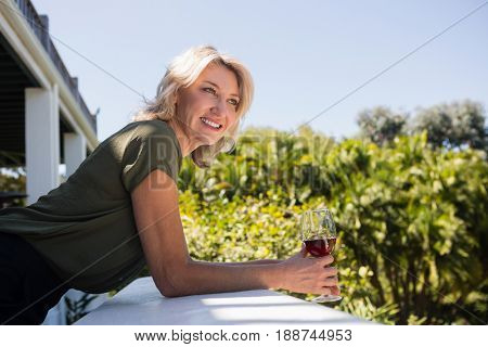Happy blond woman leaning on retaining wall in restaurant