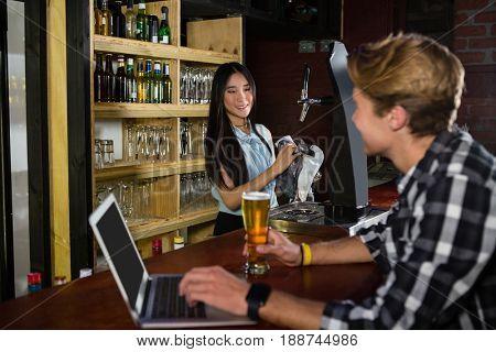 Man having beer while using laptop at bar counter