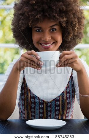 Portrait of smiling woman with frizzy hair having coffee in cafe
