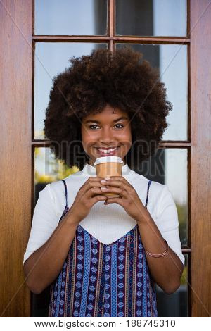 Portrait of smiling young woman holding disposable coffee cup against door