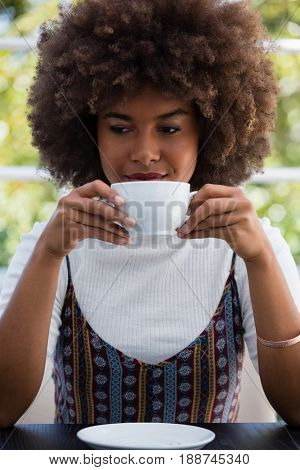 Young woman with frizzy hair having coffee in cafe
