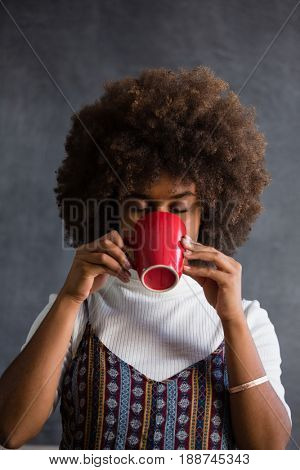 Woman with frizzy hair drinking coffee against wall