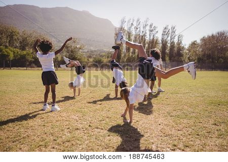 Schoolgirls performing handstand in park on a sunny day