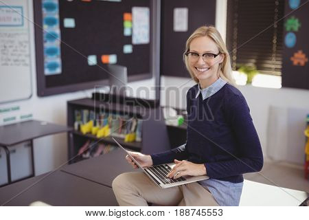 Portrait of happy teacher using laptop in classroom at school