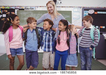 Happy teacher standing with schoolkid in classroom at school