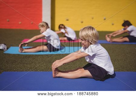 Schoolkids performing stretching exercise in schoolyard