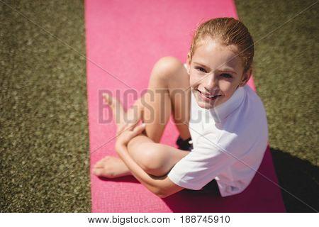 Portrait of happy schoolgirl sitting on exercise mat in schoolyard