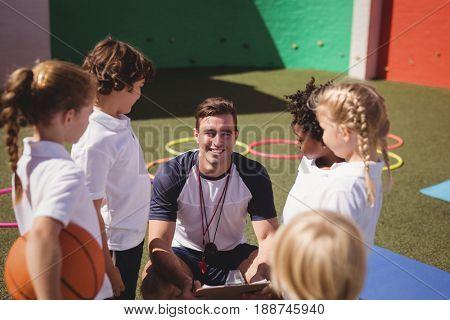 Happy coach with schoolkids in schoolyard