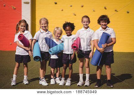 Portrait of smiling schoolgirls standing with exercise mat in schoolyard