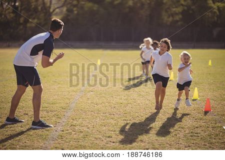 Coach monitoring schoolgirls during running competition in park