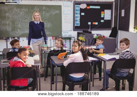 Portrait of smiling teacher and schoolkids in classroom at school