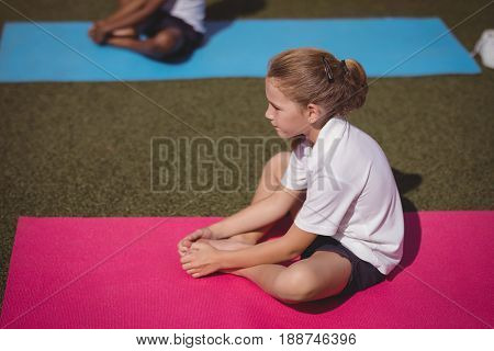 Attentive schoolgirl exercising in schoolyard