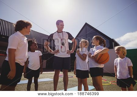 Smiling coach and schoolkids interacting with each other in schoolyard