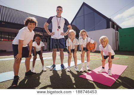 Portrait of happy coach and schoolkids in schoolyard