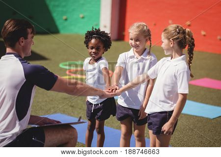 Coach and schoolkids forming handstack in schoolyard