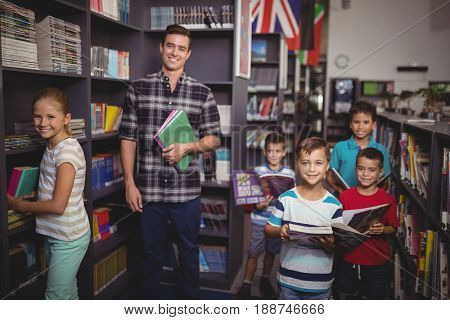 Portrait of happy teacher and schoolkids standing with books in library at school