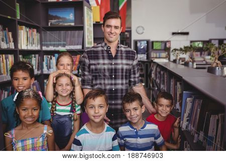 Portrait of happy teacher and schoolkids standing together in library at school