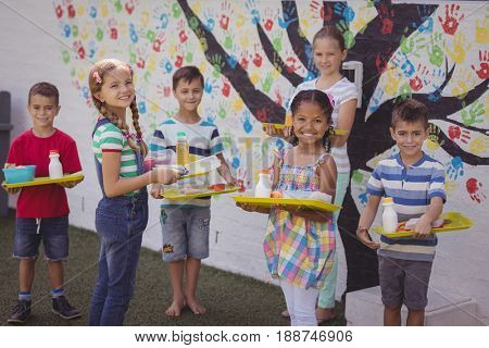 Portrait of happy schoolkids holding meal in tray at school