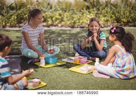 Happy schoolkids interacting while having meal in schoolyard at school