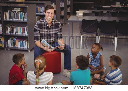 Happy teacher teaching schoolkids in library at school